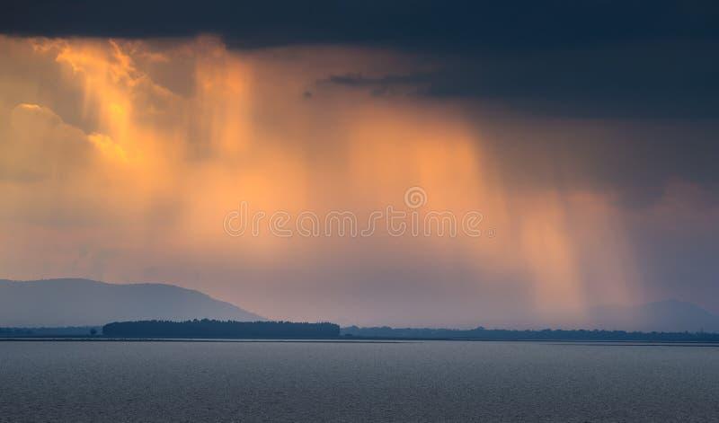 太阳射线击穿在湖的风雨如磐的云彩在金黄太阳 库存图片