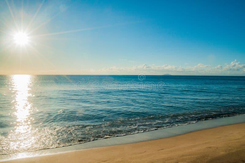太阳射线在海滩的早晨 免版税库存照片