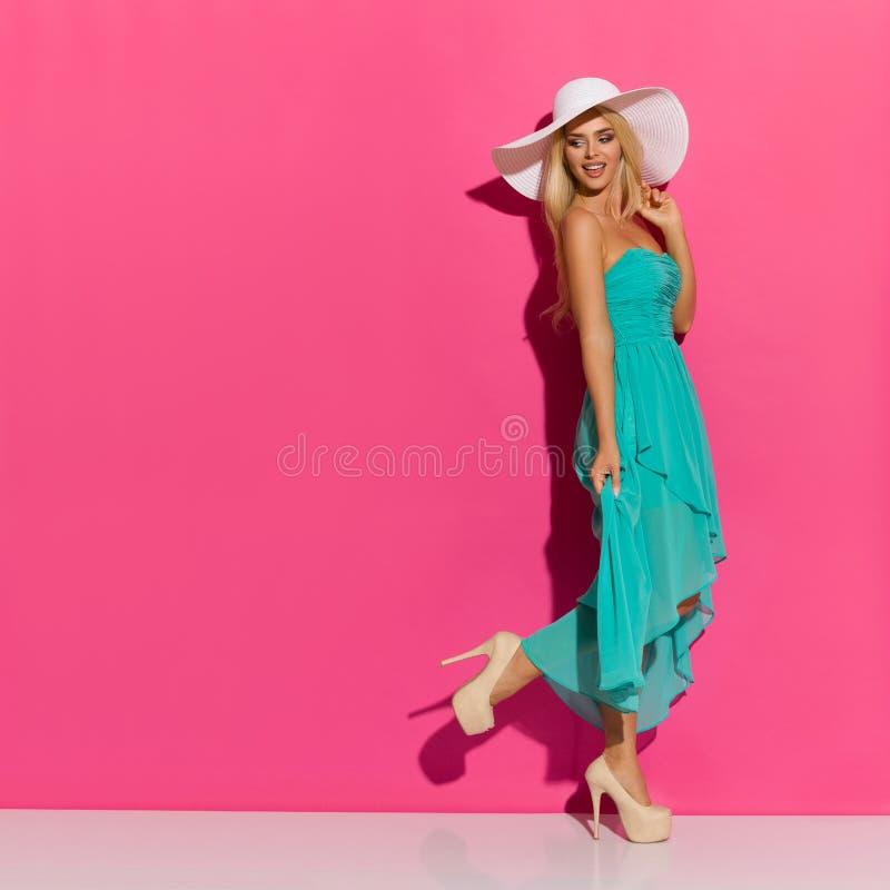 太阳帽子、绿松石礼服和高跟鞋的走的美丽的白肤金发的妇女 图库摄影