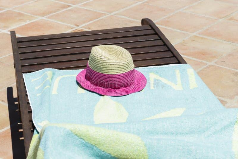 太阳帽子和浅兰的毛巾在木太阳可躺式椅 免版税库存图片