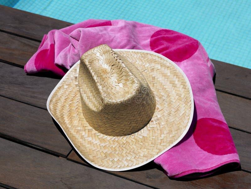 太阳帽子和海滩毛巾由游泳池 图库摄影