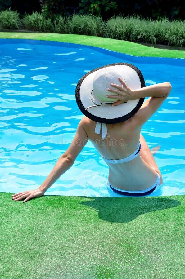 太阳帽子的放松在水池的,背面图性感的妇女 免版税库存图片