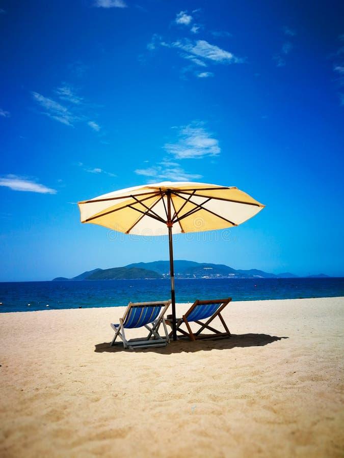 太阳懒人和伞在海滩,由海 在芽庄市海滩在夏天和好日子 库存图片