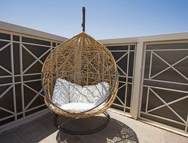 太阳懒人在大阳台区域的蛋椅子 免版税库存照片