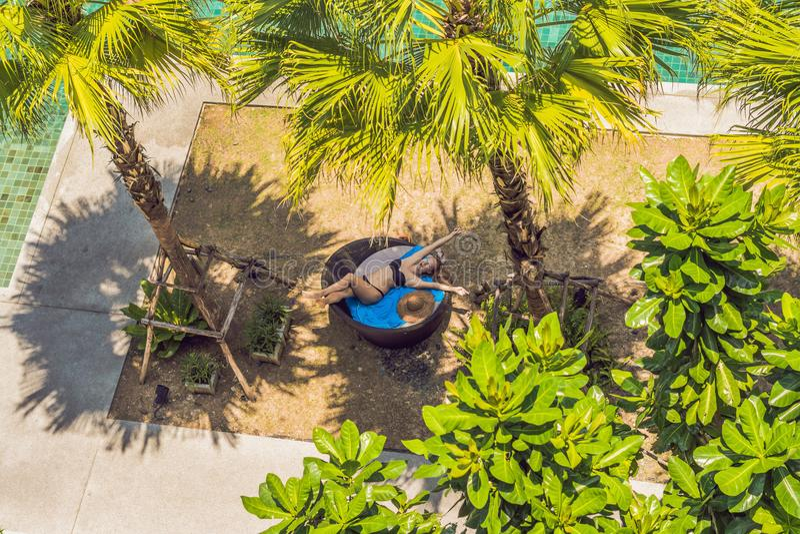 太阳懒人的女孩在游泳池附近的棕榈树中 免版税库存图片