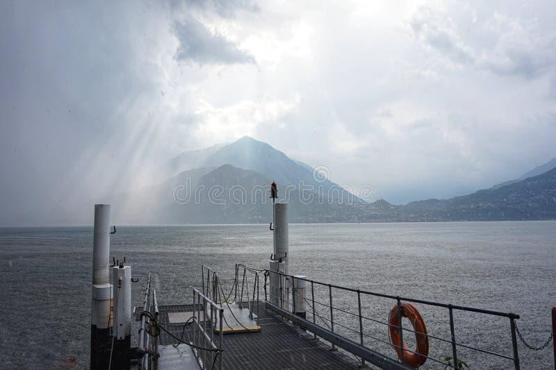 太阳打破雷云 从码头的看法在科莫湖 免版税库存图片