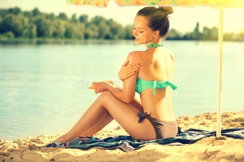 太阳晒黑 应用晒黑化妆水的秀丽少妇 应用在她的皮肤的美丽的愉快的逗人喜爱的女孩遮光剂太阳奶油 库存图片