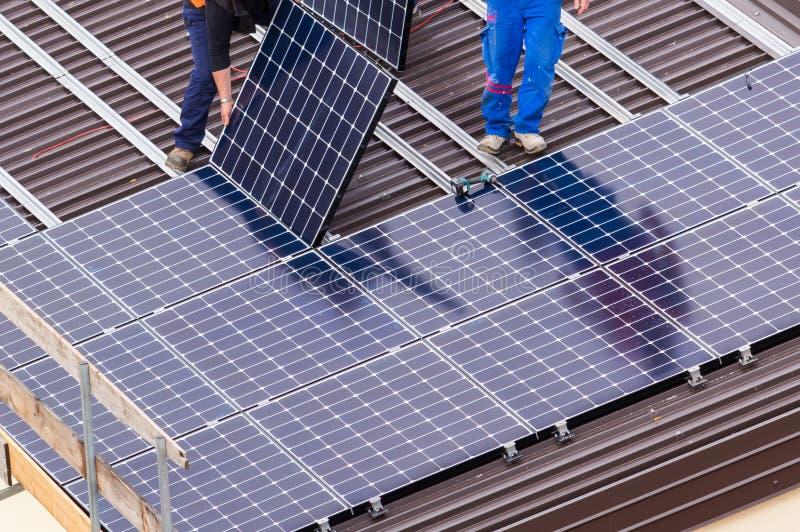 太阳电池板和工作者 免版税图库摄影