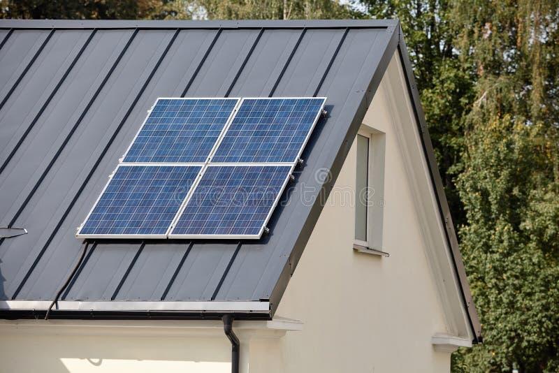 太阳电池板安装和在使用中为可更新的生态干净的绿色能量在农村家黑暗的金属屋顶  免版税图库摄影