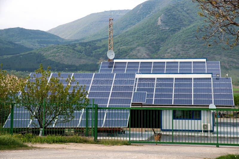 太阳电池板,在一排工厂厂房的屋顶的photovoltaics -供选择的电来源 免版税库存图片