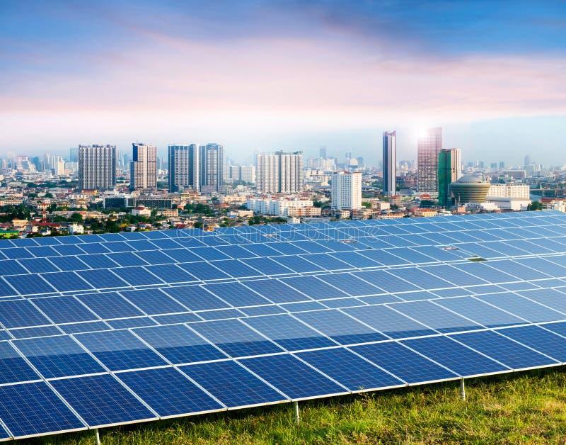太阳电池板,在背景的都市风景 库存图片
