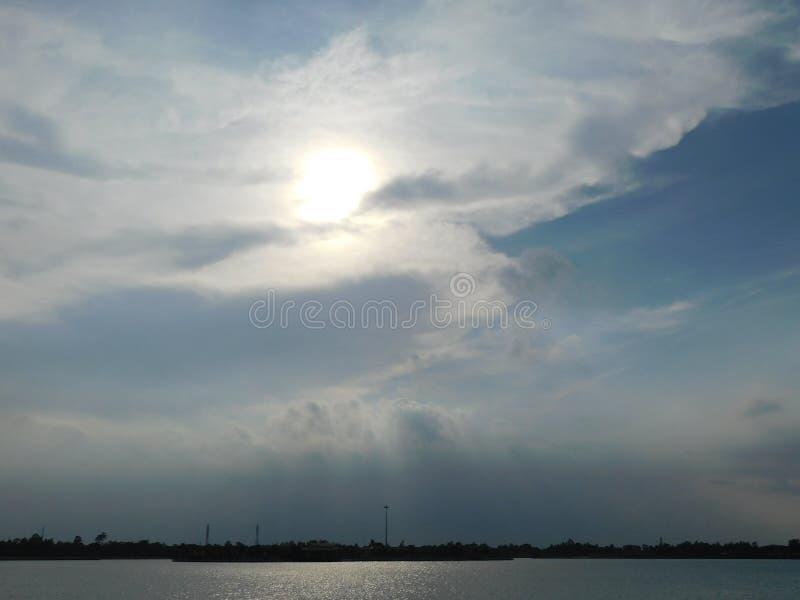 太阳的一张美丽的照片在的云彩和河 免版税图库摄影