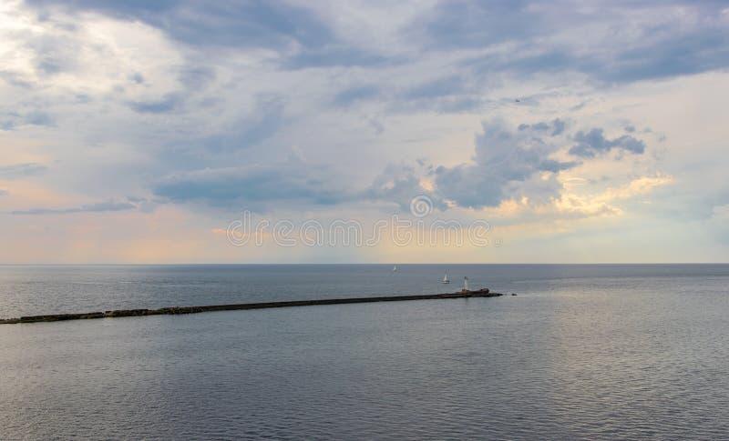 太阳的光芒通过云彩照亮海 库存图片