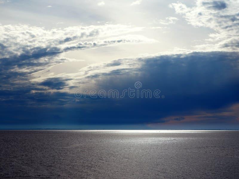 太阳的光芒通过在海的暴风云 免版税库存图片