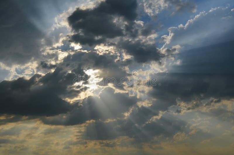 太阳的光芒通过黑暗的云彩发光 免版税库存图片