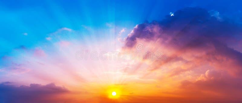 太阳的全景图片是光亮的在暮色天空和五颜六色的云彩 免版税库存照片