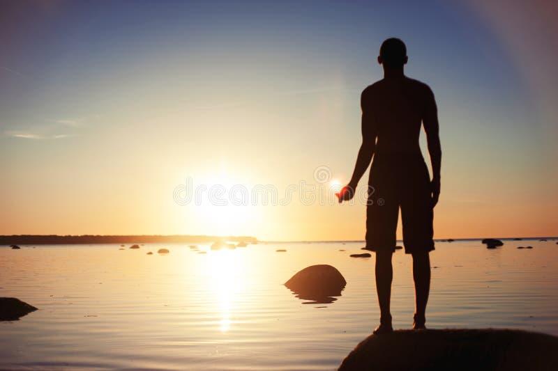 太阳的魔术 对太阳反射负的人手中 免版税库存照片