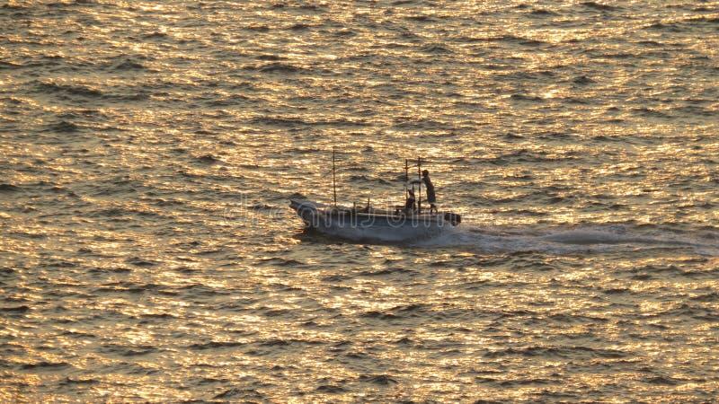太阳落山小船乘驾在晚上 免版税库存图片