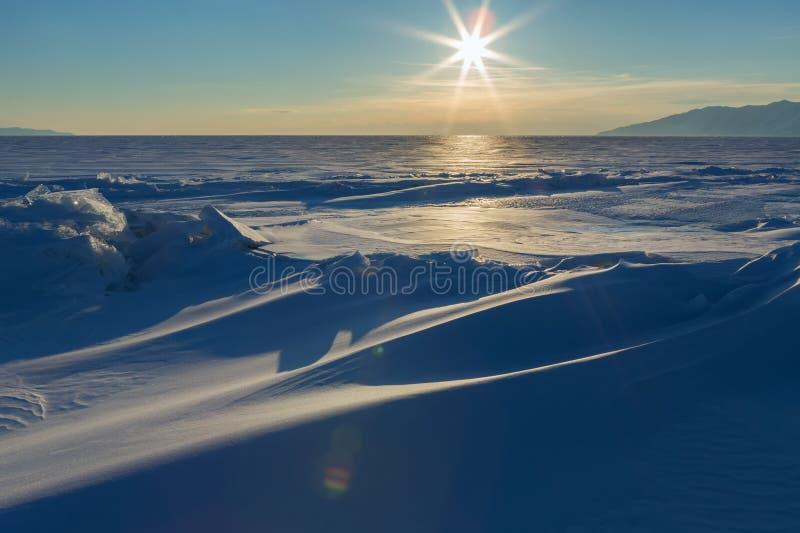 太阳设置在贝加尔湖积雪的冰小丘  免版税库存照片