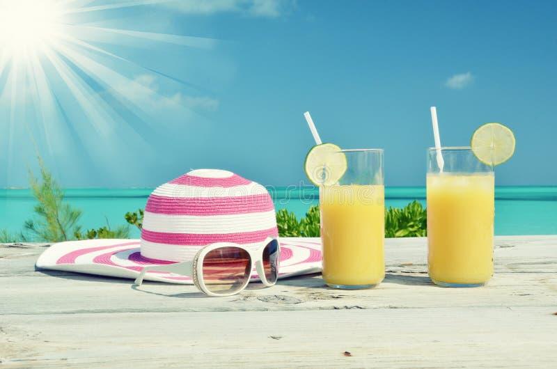 太阳镜、帽子和橙汁 库存图片