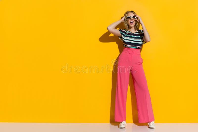 太阳镜、桃红色宽腿长裤、运动鞋和镶边女衬衫的愉快的时髦的妇女呼喊 图库摄影