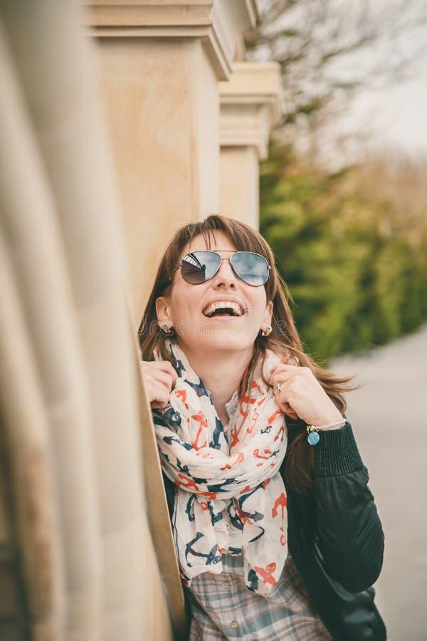 太阳镜、黑夹克和船锚围巾的年轻人微笑的愉快的女孩户外 美丽的纵向微笑的妇女 生活方式 免版税库存照片