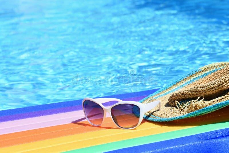 太阳镜、lilo和帽子在水在热的晴天 夏天背景为旅行和假期 田园诗的假日 免版税图库摄影
