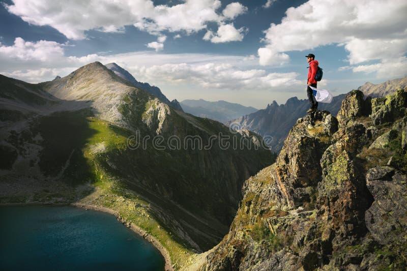 太阳镜和一个盖帽的一个有胡子的人有背包的在与白旗的上面在手中站立岩石和神色入a 免版税库存图片