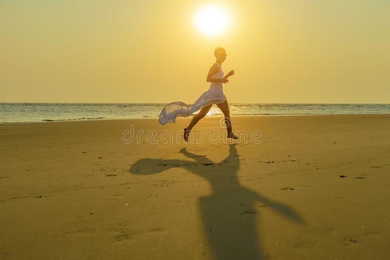 太阳镜和一件振翼的白色礼服奔跑的一名愉快的年轻白种人白肤金发的妇女在日落的海滩下 免版税库存图片