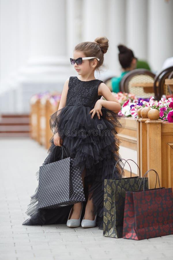 太阳镜和一件美丽的晚礼服的逗人喜爱的女孩去购物在一个有名望的精品店 免版税库存图片