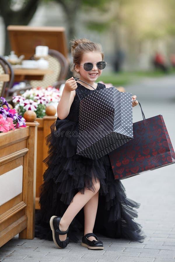 太阳镜和一件美丽的晚礼服的逗人喜爱的女孩去购物在一个有名望的精品店 免版税库存照片