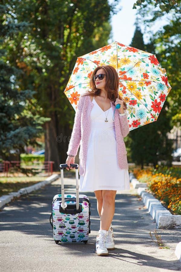 太阳镜和伞的愉快的旅游妇女带着手提箱 免版税库存图片