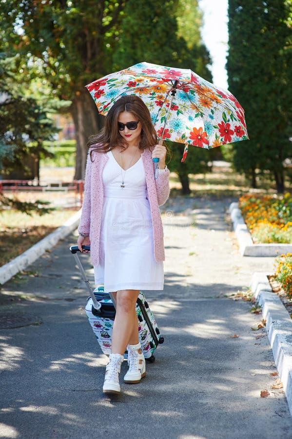 太阳镜和伞的愉快的旅游妇女带着手提箱 免版税图库摄影
