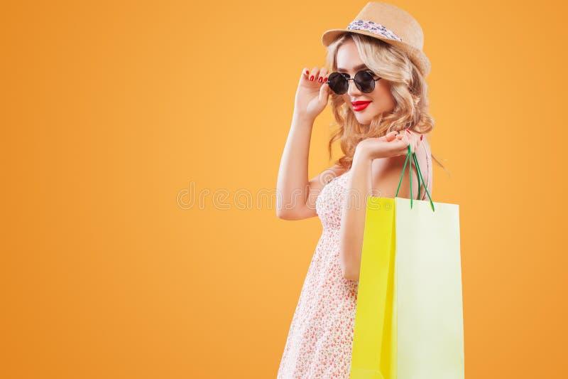 太阳镜和帽子的白肤金发的妇女有在黑星期五购物的袋子的 复制空间待售广告 免版税库存图片