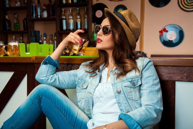 太阳镜和帽子的端庄的妇女喝冷的酒精cockta的 库存图片
