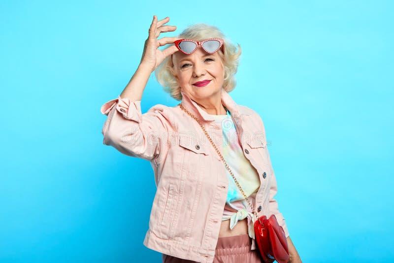 太阳镜和时髦衣裳的时髦的年长妇女微笑着 免版税图库摄影