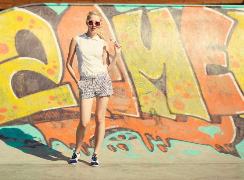 太阳镜和棒棒糖的美丽的年轻白肤金发的妇女在街道画背景站立 定调子在温暖的颜色 免版税库存图片