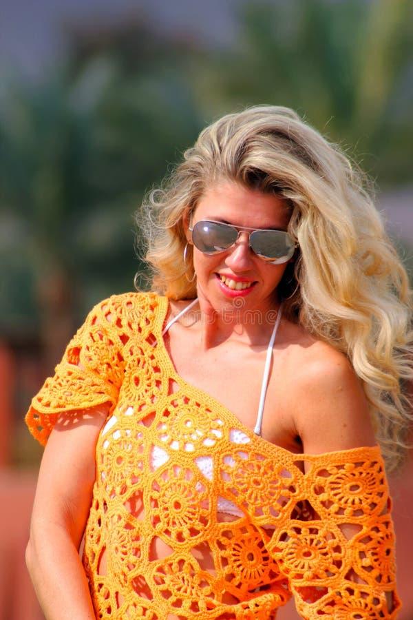 太阳镜和橙色礼服的画象白肤金发的女孩 图库摄影