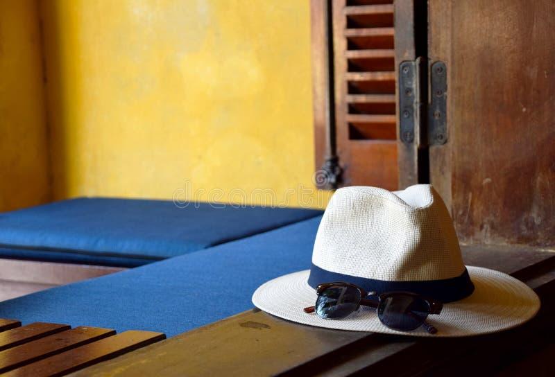 太阳镜和海滩帽子在窗口边缘 免版税库存图片