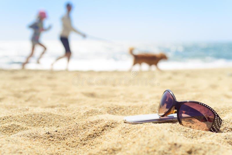 太阳镜和电话在海滩与人背景的 库存照片