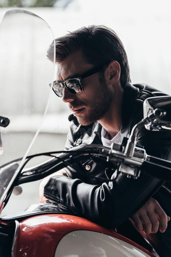 太阳镜和皮夹克的英俊的时髦的年轻人坐摩托车 库存照片