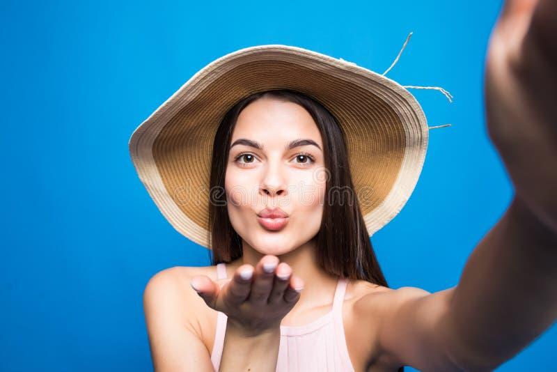太阳镜和草帽的年轻可爱的女孩送空气亲吻到selfie照相机 有红色嘴唇的好嬉戏和愉快的妇女在b 图库摄影