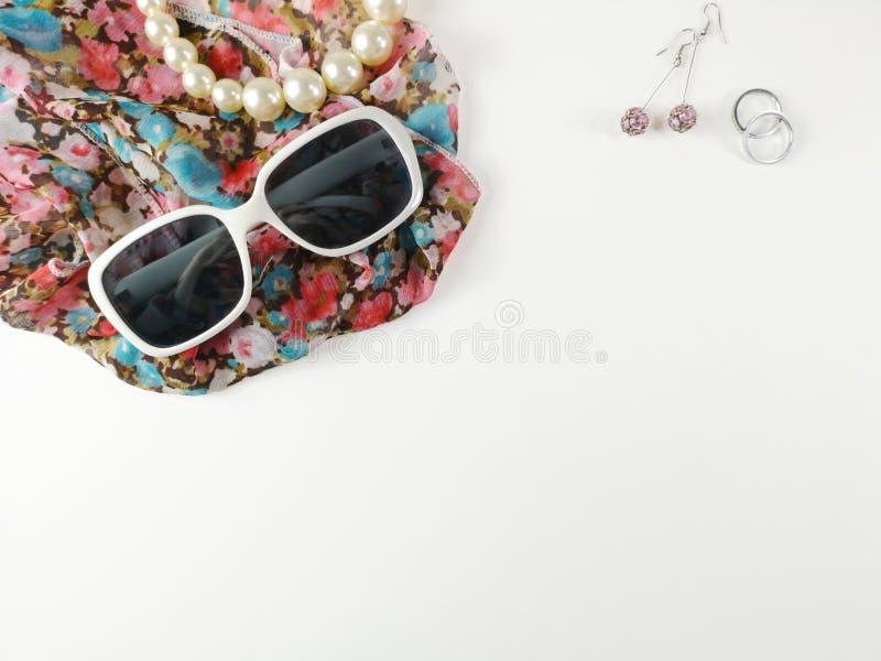 太阳镜和项链由珍珠制成,安置在时尚面纱和耳环 免版税图库摄影