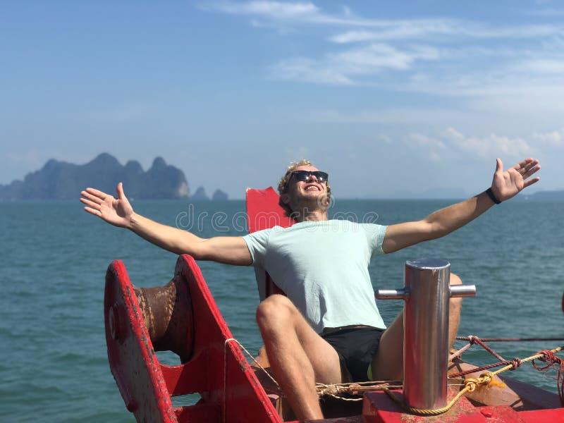 太阳镜和T恤杉的一个白肤金发的人对太阳张开了他的手在船上在一热的天以为背景 库存图片