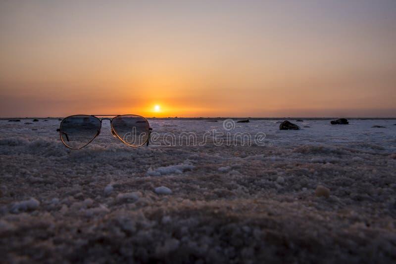 太阳镜在日落的盐沼 免版税库存图片