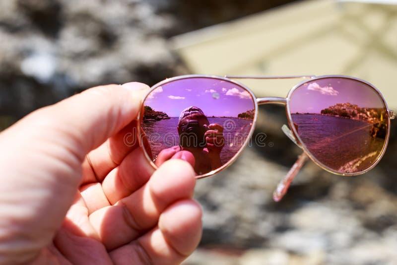 太阳镜在海滩的女性手上与她自己与照相机反射 库存照片