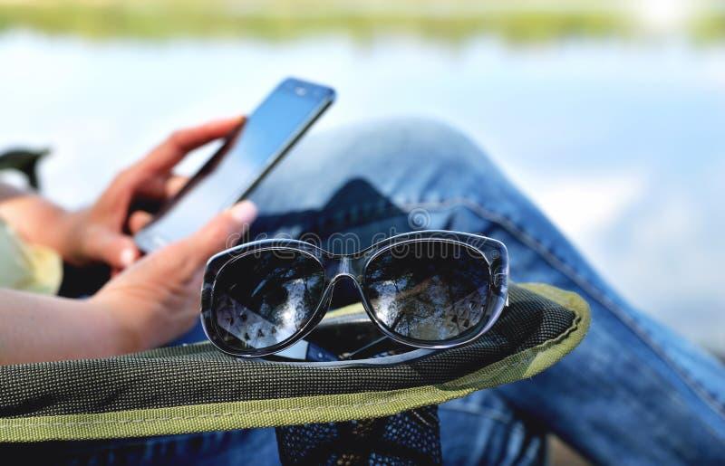 太阳镜在躺椅的扶手说谎,扶手椅子的女孩看一个手机衬托 免版税库存图片