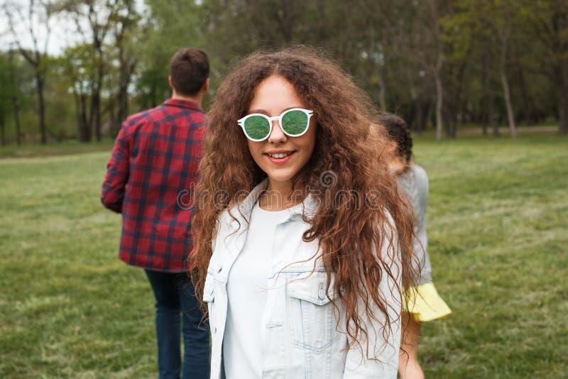 太阳镜微笑的卷发的女孩 库存图片