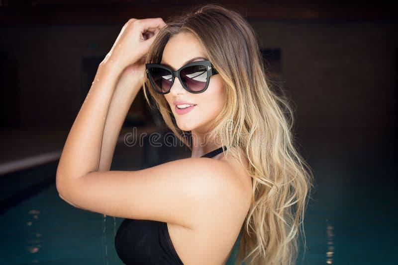 太阳镜摆在的性感的白肤金发的妇女 免版税库存图片