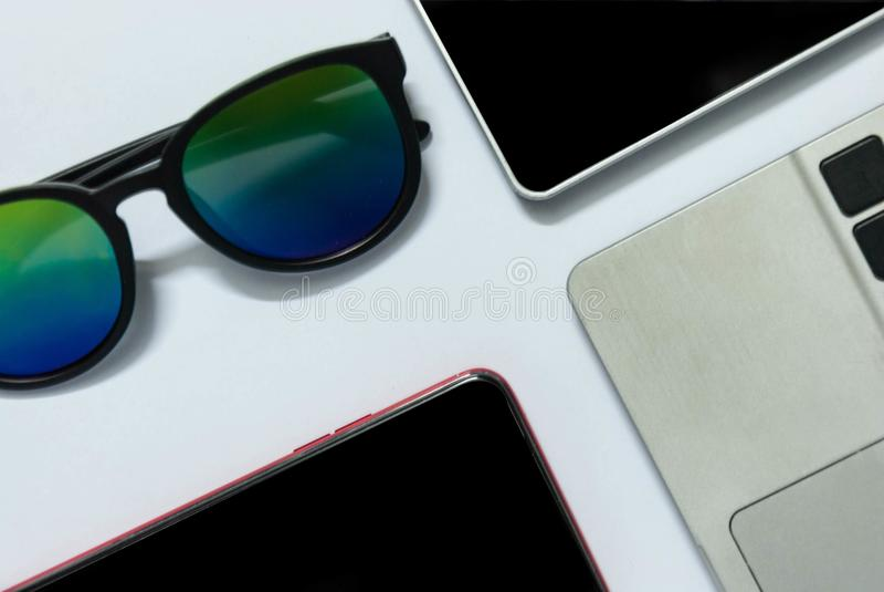 太阳镜智能手机在白色背景的片剂键盘平的位置照片  库存图片